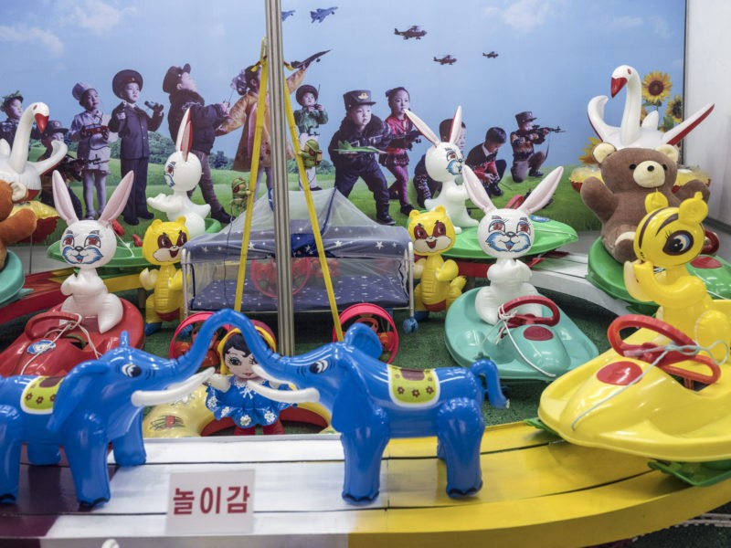 Carl De Keyzer - Toys, with a background image depicting children dressed as soldiers and doctors, playing with remote-control vehicles. Three Revolutions Exhibition. Pyongyang. 29 May 2017 4:00 PM