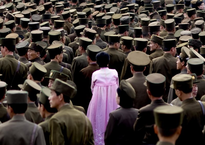 Eric Lafforgue – North Korea - A woman standing in the middle of a crowd of soldiers. This picture is not supposed to be taken as officials do not allow army pictures