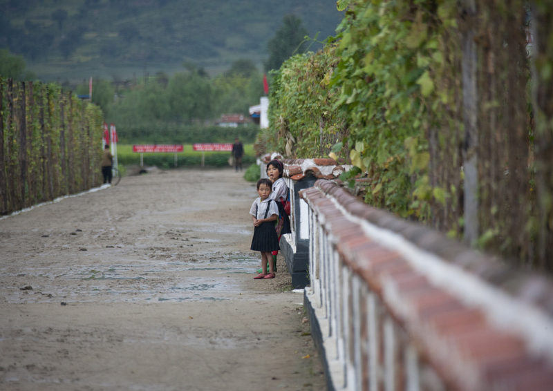 Eric Lafforgue – North Korea - Two little girls standing on a road near a farm in Hamhung